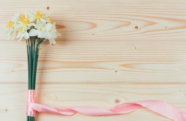 Buquê de narcisos com fita rosa na madeira com copyspace