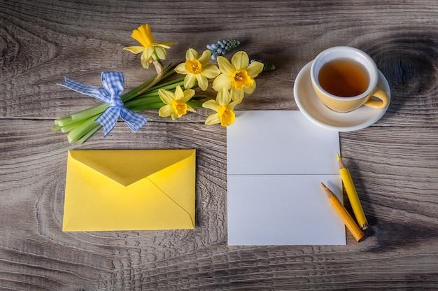 Buquê de narcisos e muscari na mesa de madeira com cartão e um envelope. layout para cartão postal ou convite. vista superior, lugar para texto, close-up.