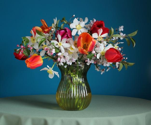 Buquê de narcisos e tulipas em cima da mesa.