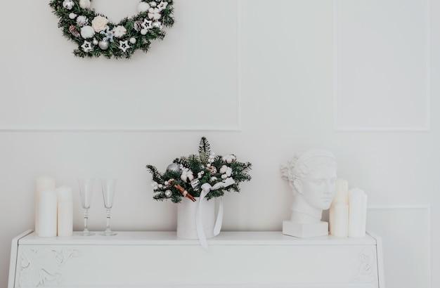Buquê de natal de abeto e algodão em um interior branco contra o fundo de um piano branco