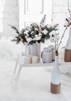Buquê de natal de abeto e algodão em um interior branco. feliz ano novo.