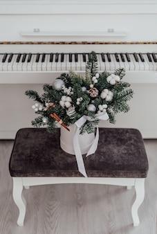 Buquê de natal de abeto e algodão no fundo de um piano branco