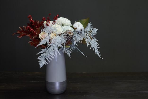 Buquê de natal e composição em um vaso de cerâmico em um foco seletivo e escuro