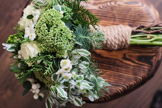 Buque de noiva. casamento. buquê de flores brancas e verdes fica em uma cadeira contra