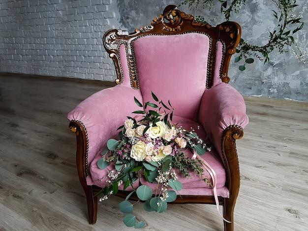 Buquê de noiva com lindos tons pastel de rosas e galhos de eucalipto em uma luxuosa poltrona de veludo rosa