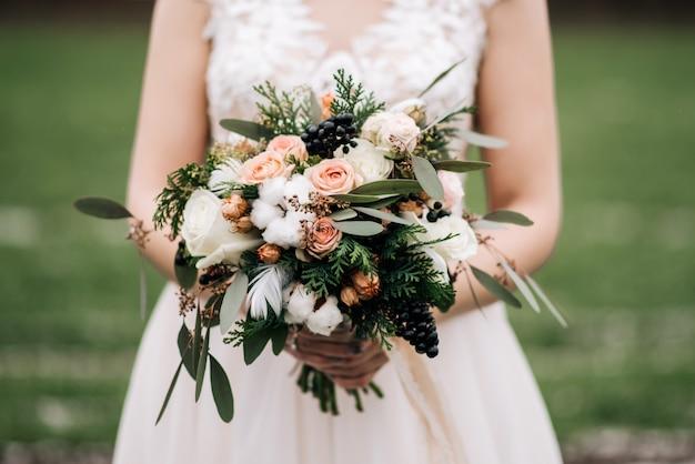 Buquê de noiva de inverno com rosas, algodão, abeto, penas, flores secas nas mãos da noiva