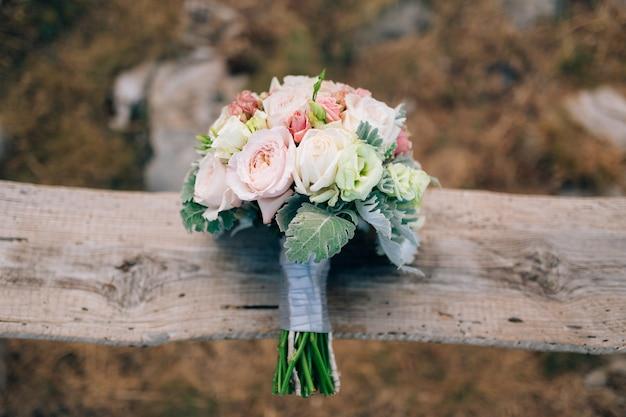 Buquê de noiva de lisianthus e cineraria silver em um velho banco de madeira feito à mão. casamento em montenegro, adriático.