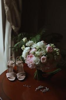 Buquê de noiva de rosas brancas e peônias com sapatos de noiva e anéis de casamento na mesa antes da cerimônia de casamento