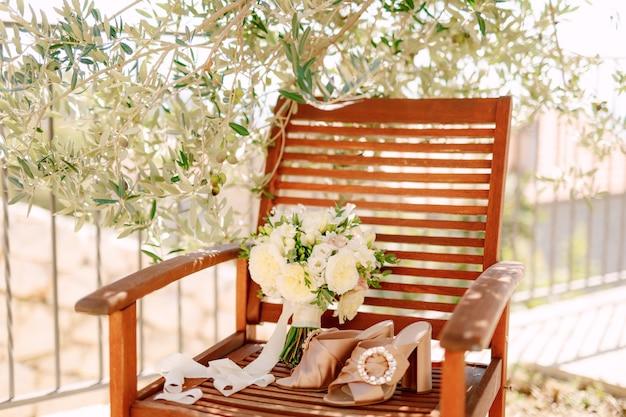 Buquê de noiva de rosas brancas, ramos de buxo de freesia e fitas brancas perto dos sapatos da noiva