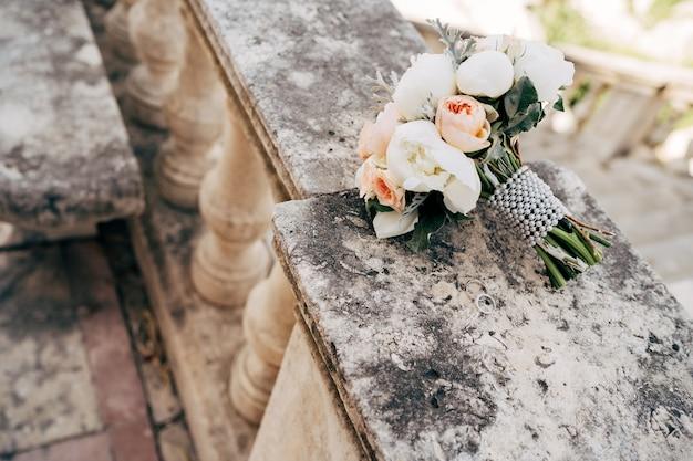 Buquê de noiva de rosas peônias brancas e creme salal artemisia com fita de pérolas no parapeito de