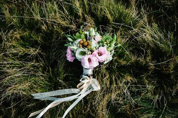Buquê de noiva deitado na grama no campo