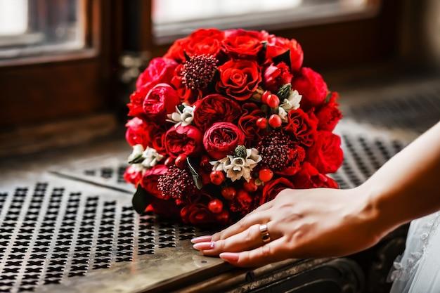 Buquê de noiva redondo de rosas vermelhas brilhantes e frutas em uma treliça de um parapeito de janela perto da mão de uma mulher.