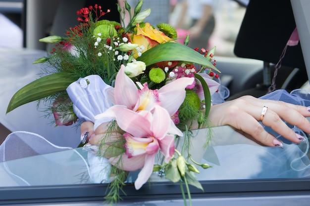Buquê de orquídeas e rosas na mão da noiva