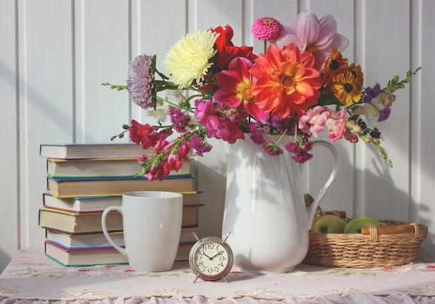Buquê de outono e livros didáticos, vida escolar ainda. composição com flores e livros.