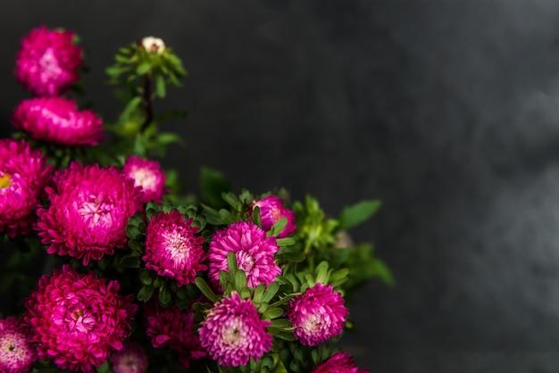 Buquê de outono flores ásteres em fundo escuro grunge