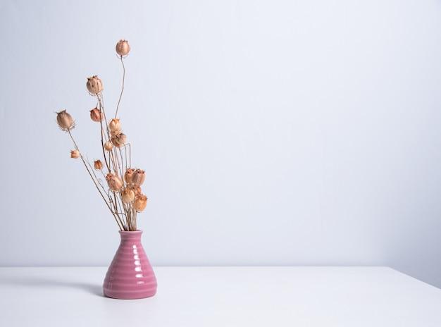 Buquê de papoilas de flores secas em um vaso rosa em um fundo branco. vista frontal e espaço de cópia