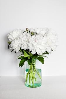 Buquê de peônias brancas em um vaso de vidro no fundo da parede branca