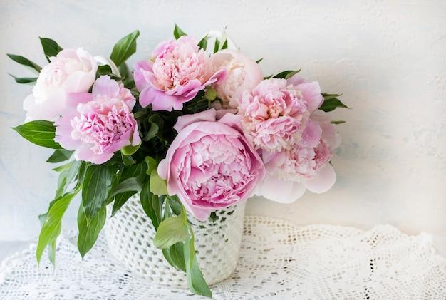 Buquê de peônias rosa em uma mesa de madeira em uma cesta artesanal na toalha de mesa de renda