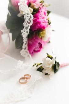 Buquê de peônias rosa linda e anéis de casamento mentem sobre uma mesa branca.