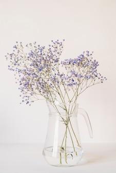 Buquê de pequenas flores azuis jarro de vidro