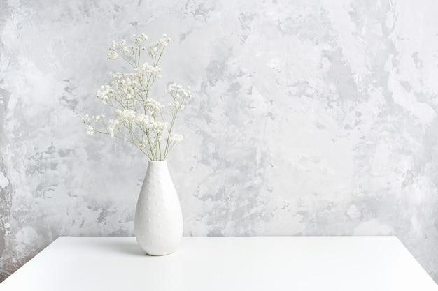 Buquê de pequenas flores brancas delicadas em um vaso na mesa contra a parede de pedra cinza