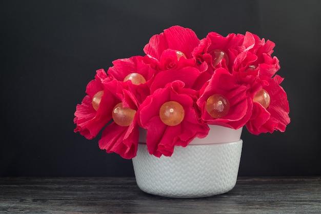 Buquê de pirulitos saborosos em um vaso na mesa de madeira. flores doces