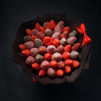 Buquê de presente coletados de morangos maduros cobertos com chocolate marrom em um fundo preto