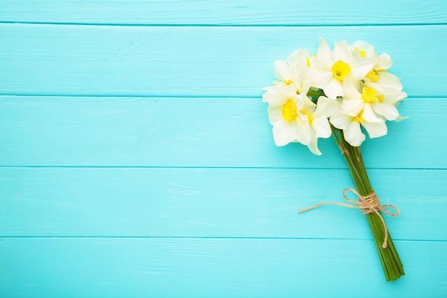 Buquê de primavera de narciso na parede de madeira azul