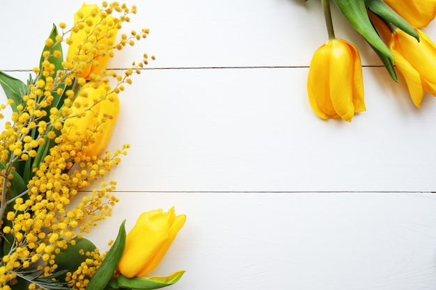 Buquê de primavera de tulipas amarelas e flores de mimosa. dia das mães, 8 de março ou conceito de páscoa.