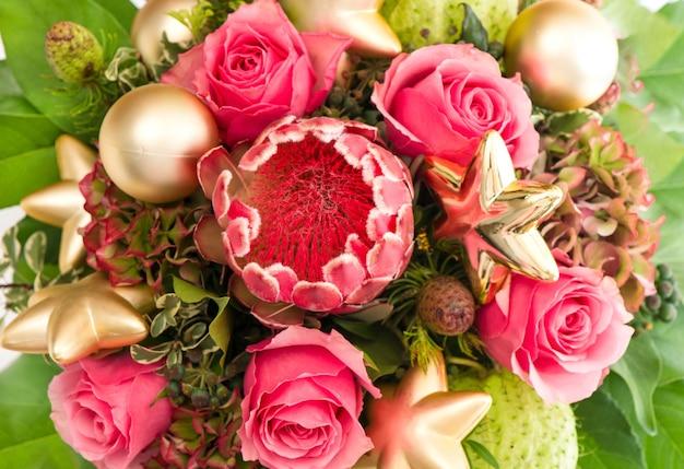 Buquê de proteas de flores exóticas e rosas frescas com decoração de natal dourada