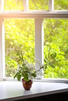 Buquê de ramos de flor de cereja de pássaro em um vaso de cerâmica na mesa de madeira branca no interior de estilo vintage.