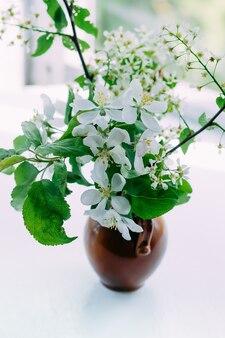 Buquê de ramos de flor de cereja de pássaro em um vaso de cerâmica na mesa de madeira branca