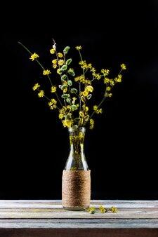 Buquê de ramos de flores de salgueiro e dogwood em um vaso na mesa em um fundo preto
