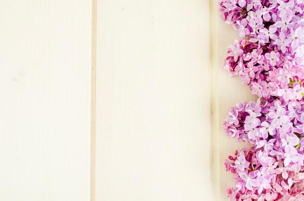 Buquê de ramos lilás brancos e roxos no fundo da mesa de madeira