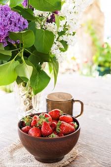 Buquê de ramos lilás em vaso de cristal, tigela de barro com morango vermelho e copo de vidro escuro na mesa de madeira.