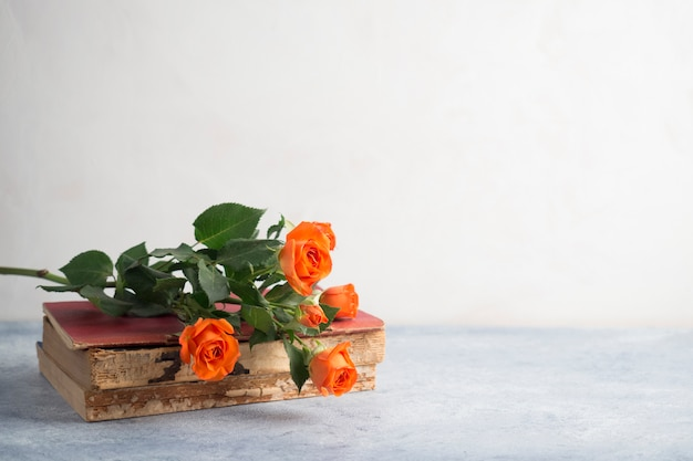 Buquê de rosa colocado na pilha de livros antigos
