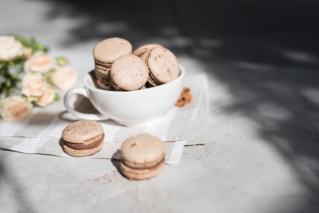 Buquê de rosa com tigela de biscoitos sobre o pano de fundo texturizado concreto