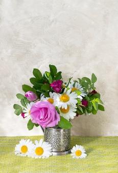 Buquê de rosa mosqueta e camomila. buquê de flores no jardim de verão. natureza morta com margaridas