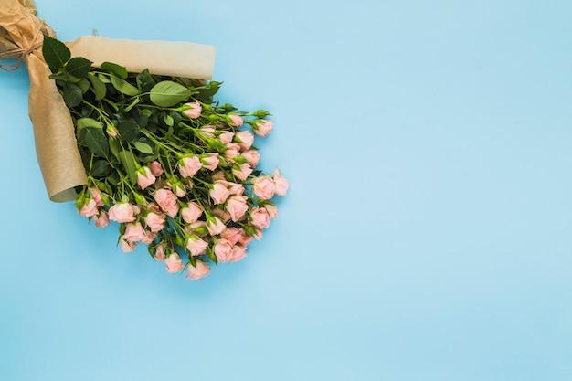 Buquê de rosa rosa embrulhado em papel pardo sobre fundo azul