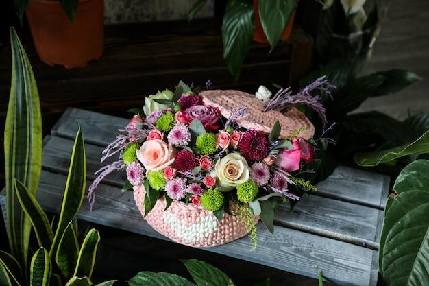 Buquê de rosa vista lateral com flores silvestres em uma cesta rosa