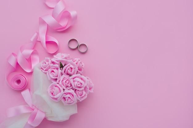 Buquê de rosas, alianças e fita rosa