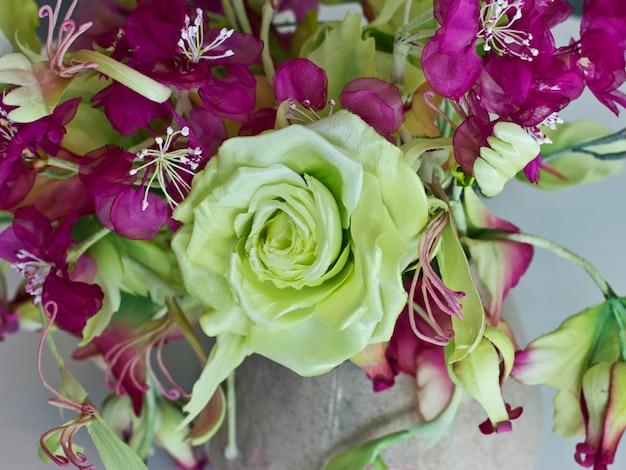Buquê de rosas amarelas com flores vermelhas com botões em um vaso em uma mesa branca