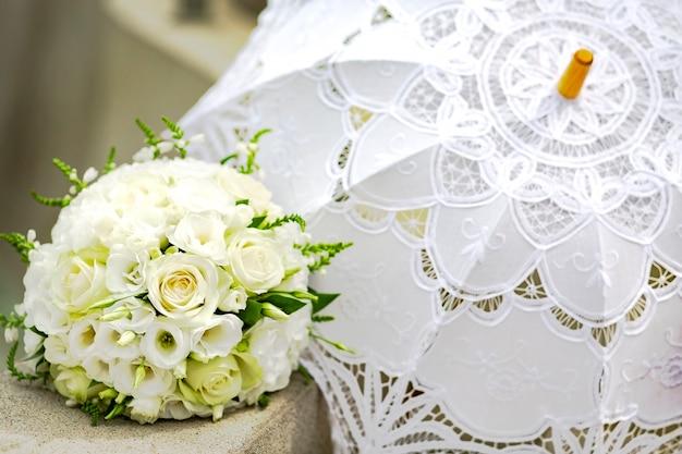 Buquê de rosas brancas e eustomas de noiva e um guarda-chuva de renda branca são acessórios de casamento