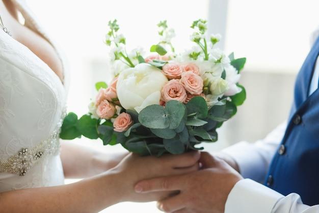 Buquê de rosas brancas e peônia nas mãos de recém-casados.