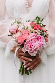 Buquê de rosas brancas e rosa e peônias nas mãos da noiva no fundo de um vestido branco