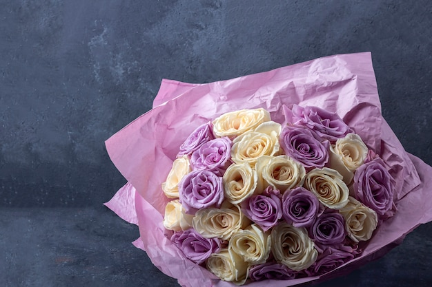 Buquê de rosas brancas e roxas incríveis surpreendentes em papel ofício em fundo escuro