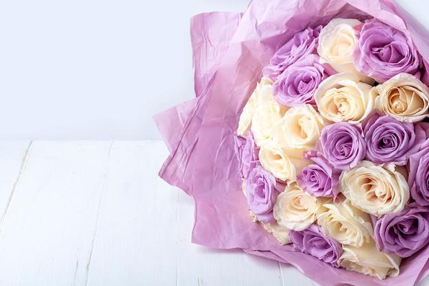 Buquê de rosas brancas e roxas surpreendentes frescas em papel ofício em fundo branco para cartão postal, capa, banner.