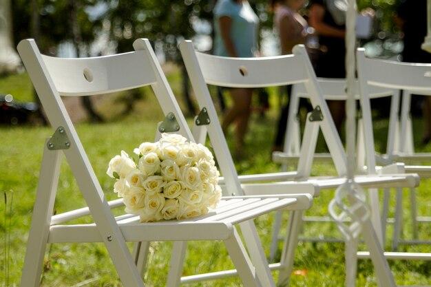 Buquê de rosas brancas encontra-se em uma cadeira em uma parede verde