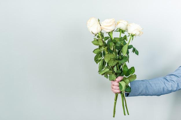 Buquê de rosas brancas nas mãos. dia dos namorados