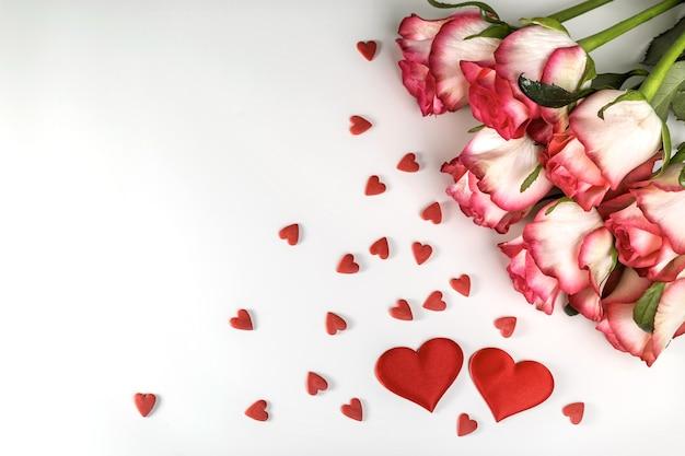 Buquê de rosas brilhantes e corações vermelhos em um fundo branco. cartão de dia dos namorados.